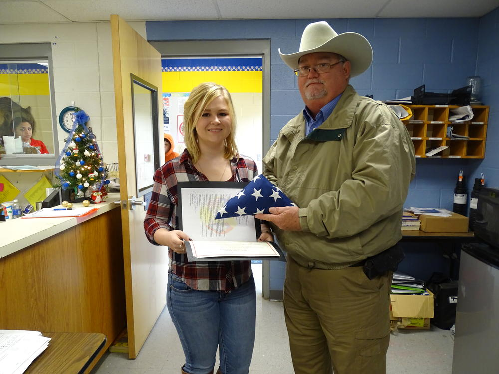 Sheriff Singleton presenting folded flag and paperwork to female high school student