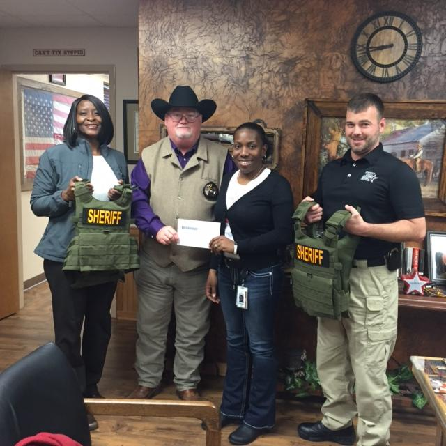 Pam Gibbs, Sheriff Singleton, Andrea Hale, and Justin Crane standing with vests