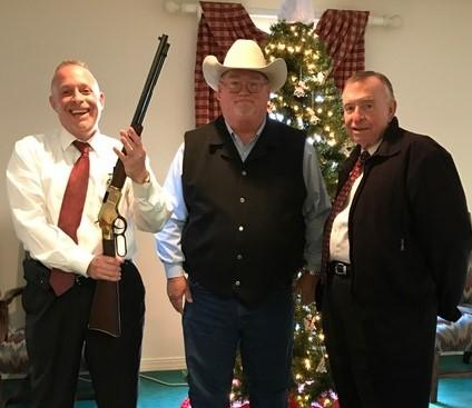 Two men in suits, one holding a shotgun pointed at the ceiling, standing on either side of Sheriff Singleton