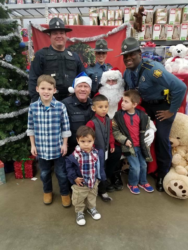Sheriff's Office staff and young children sitting with Santa