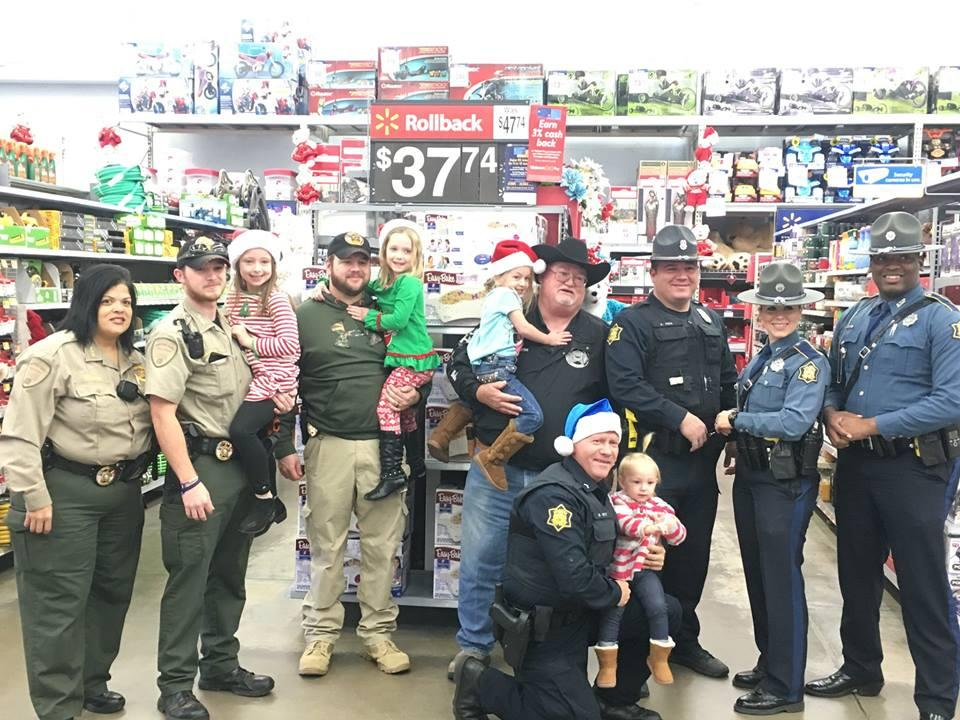 Sheriff's Office staff and young children standing in walmart aisle smiling