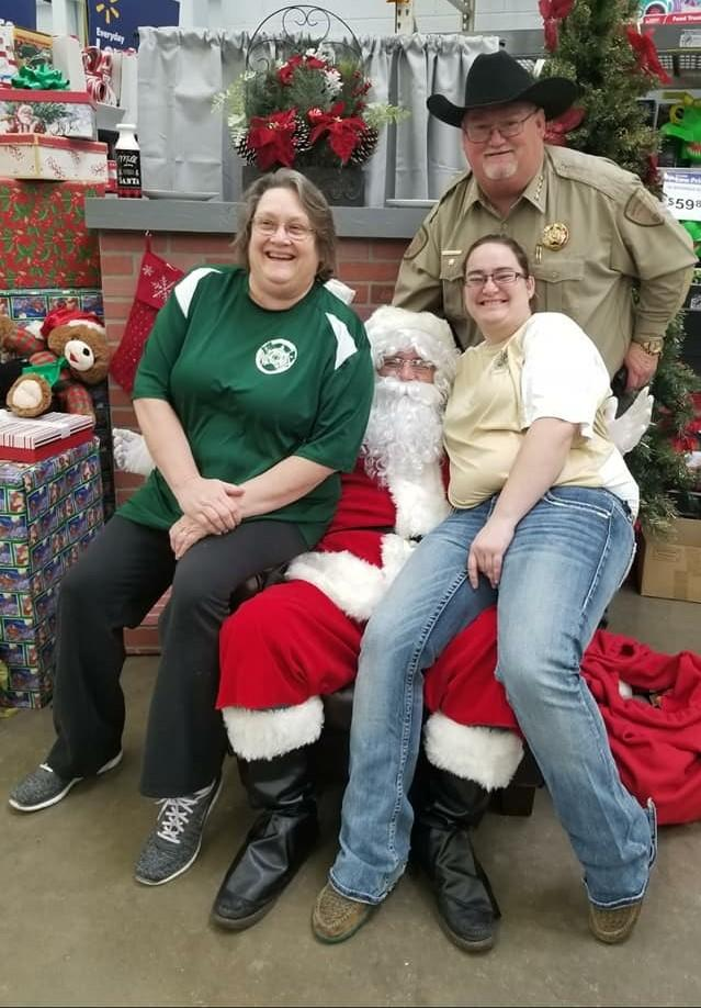 Sheriff Singleton with Santa and two women