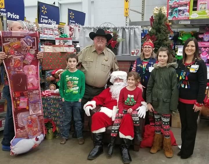Sheriff with Santa giving a family a gift