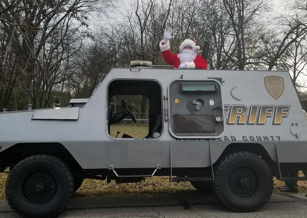 Santa standing out of a sheriff vehicle