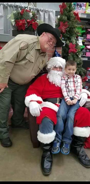 Sheriff with Santa who has a child on his lap