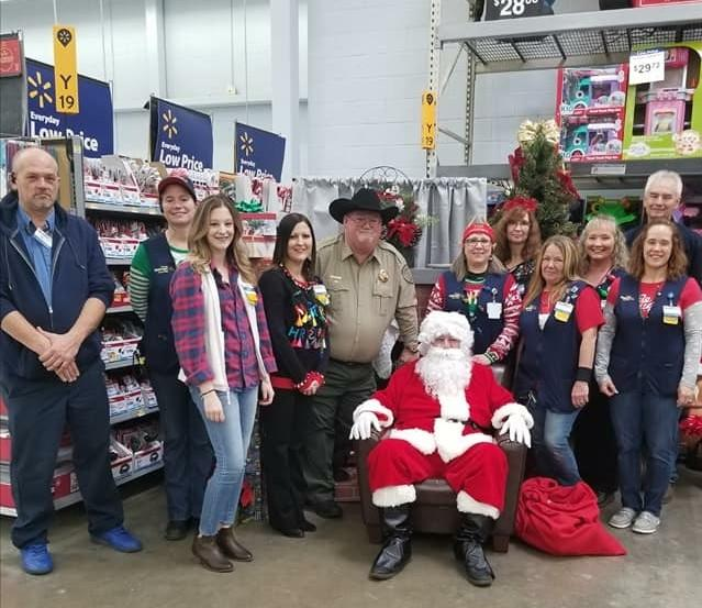 Sheriff's office staff and walmart staff standing with Santa Claus