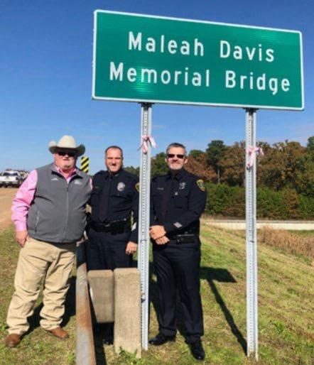 Officers with the Maleah Davis Memorial Bridge Sign